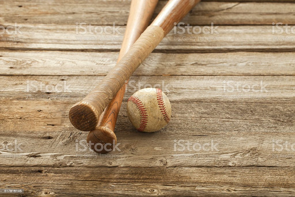 Old baseball and bats on rough wood surface stock photo