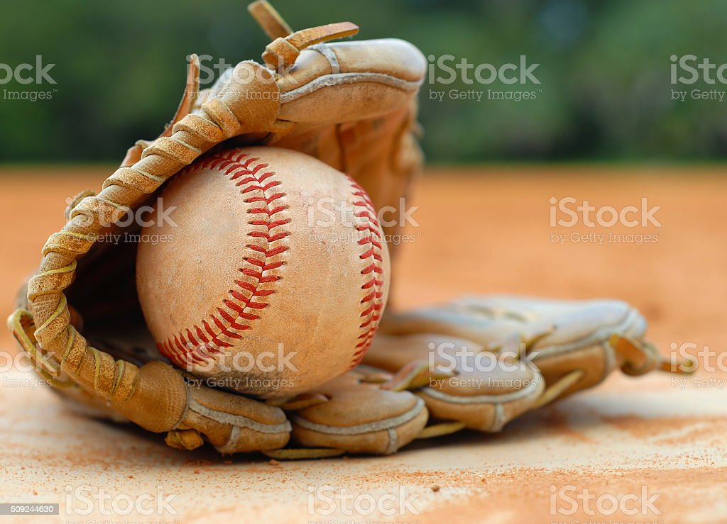 Close up detail of an old, worn baseball and leather glove laying on...
