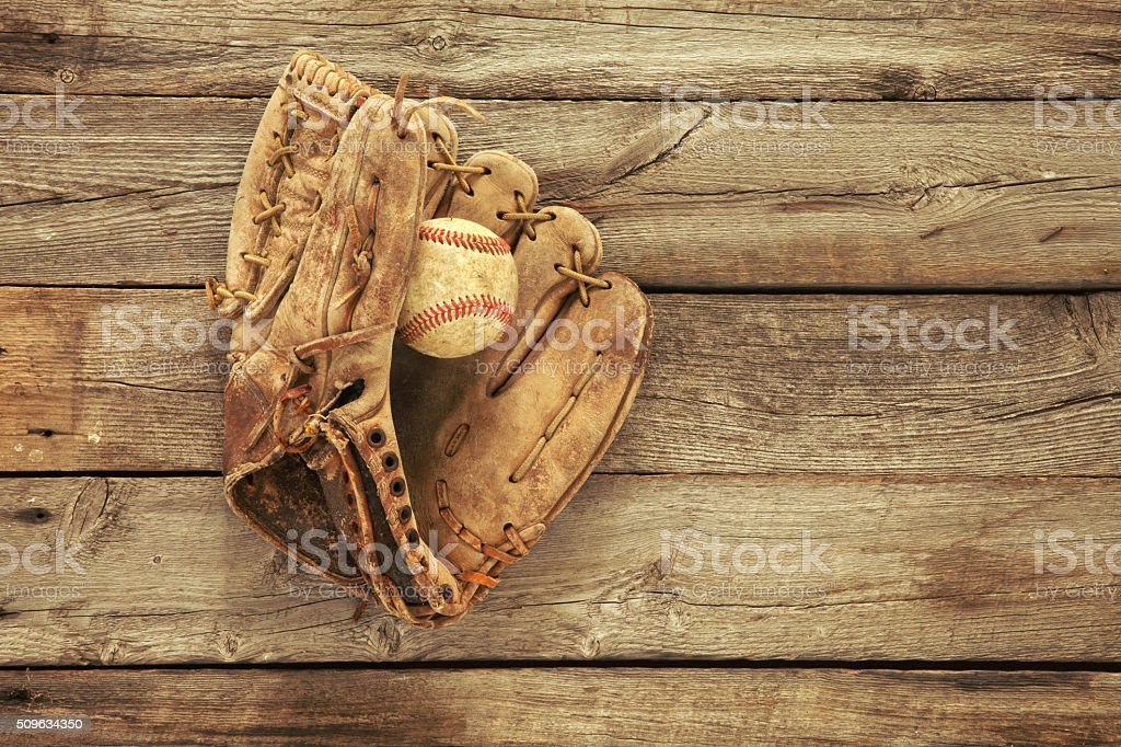 Old baseball and mitt on rough wood background stock photo