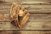 Old baseball and mitt on rough wood background