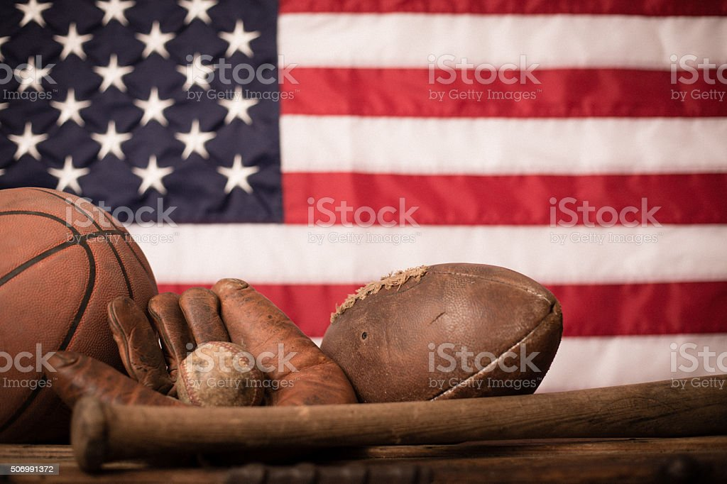 Old Baseball, Football and Basketball Sports Equipment with American Flag stock photo