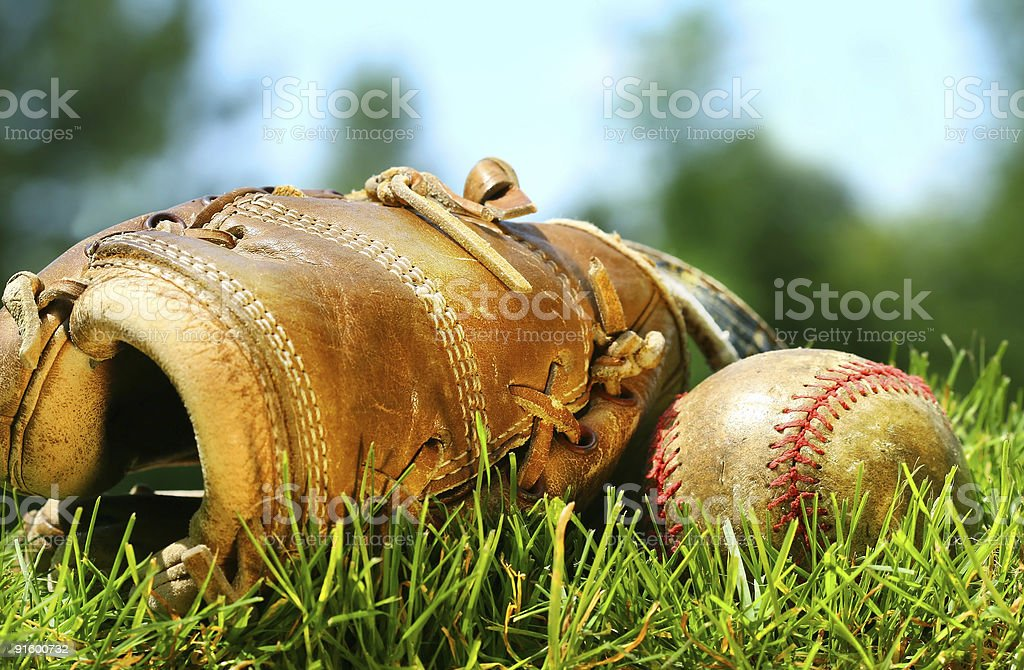 Old baseball glove and ball on the grass royalty-free stock photo
