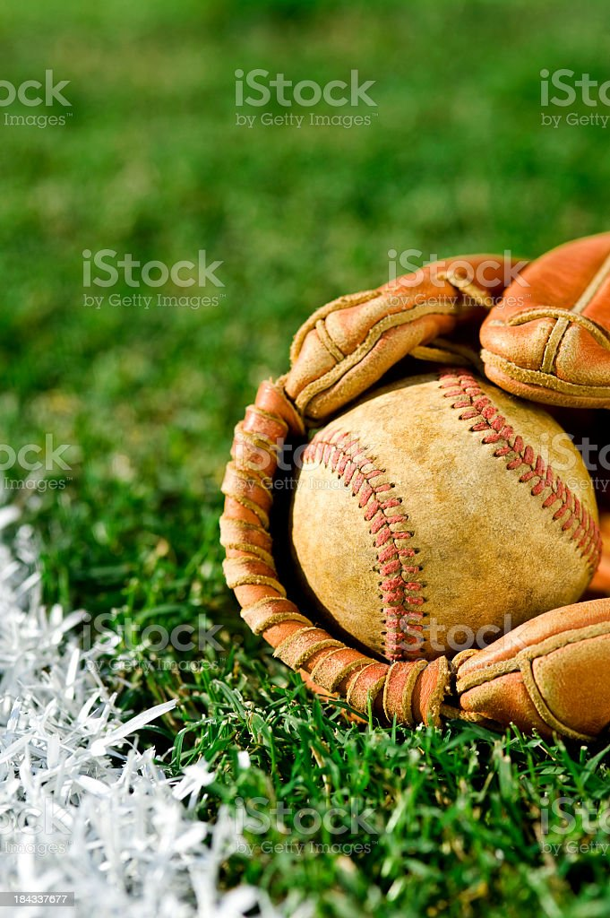 Old Baseball in a worn glove along foul line stock photo
