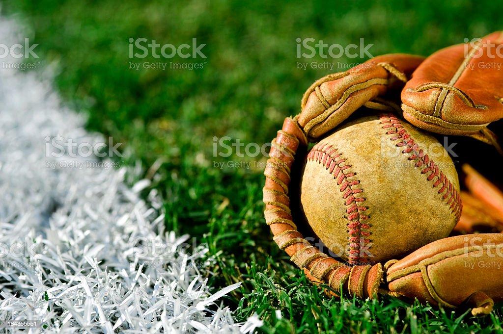 Old Baseball in glove along foul line stock photo
