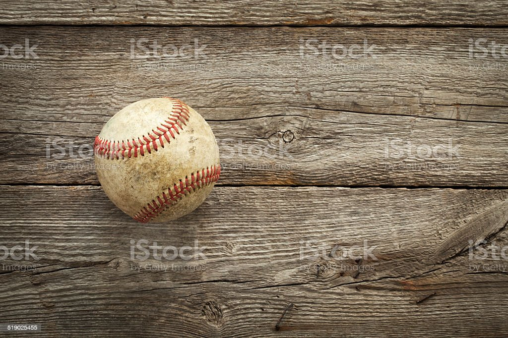 Old baseball on rough wood surface stock photo