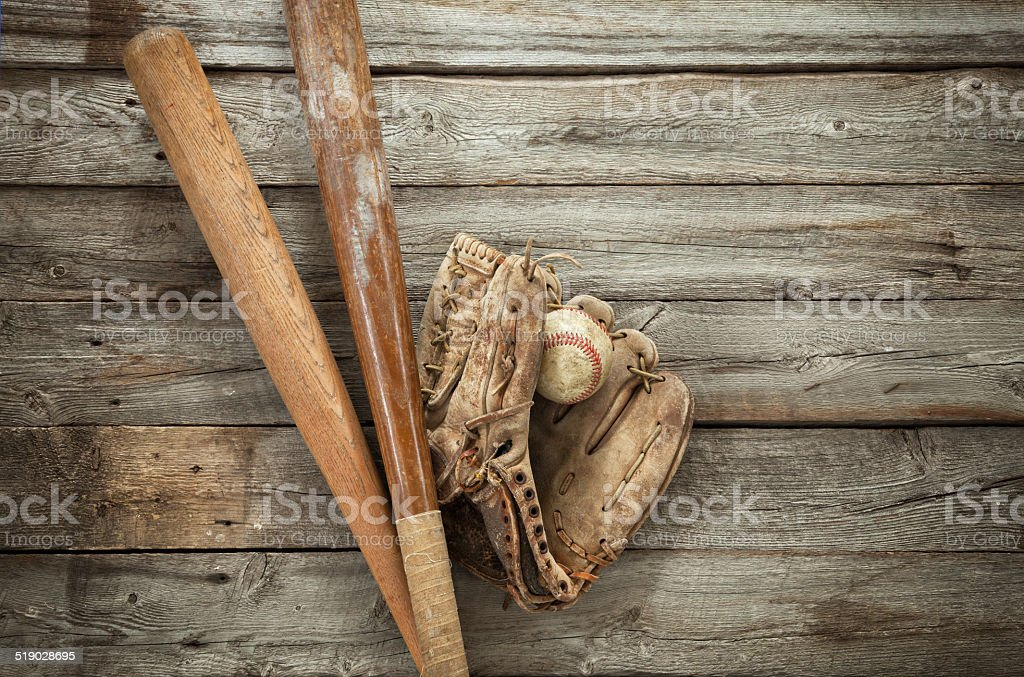 Old baseball with mitt and bats on rough wood stock photo