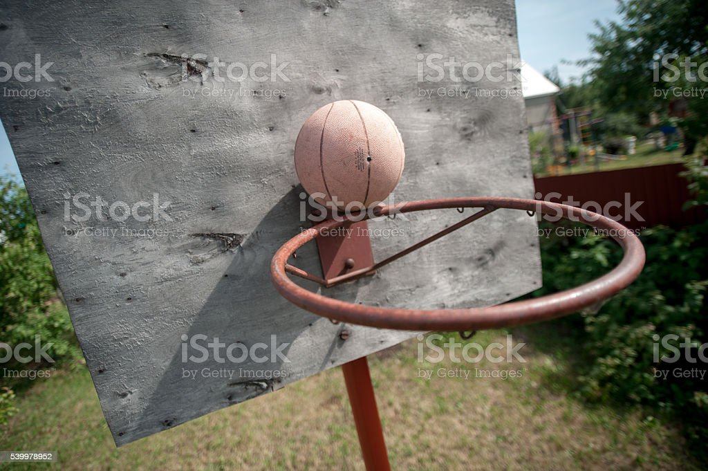 old basketball and basket on weathered wooden facade stock photo