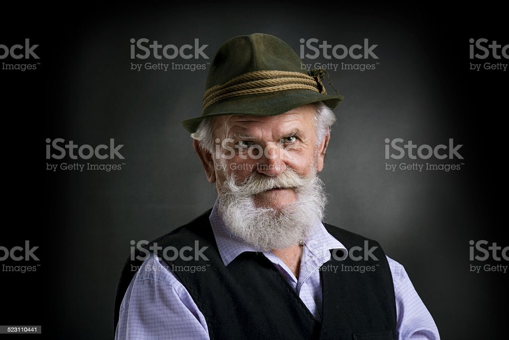 Old bavarian man in hat on black background stock photo