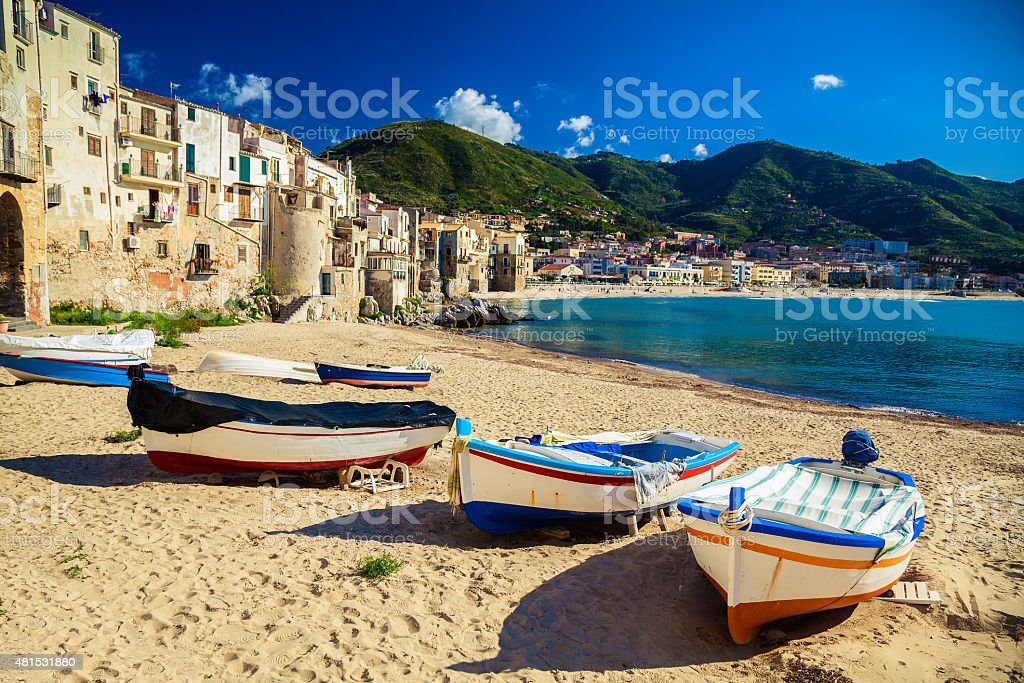 Old beach in Cefalu with fishing boats stock photo