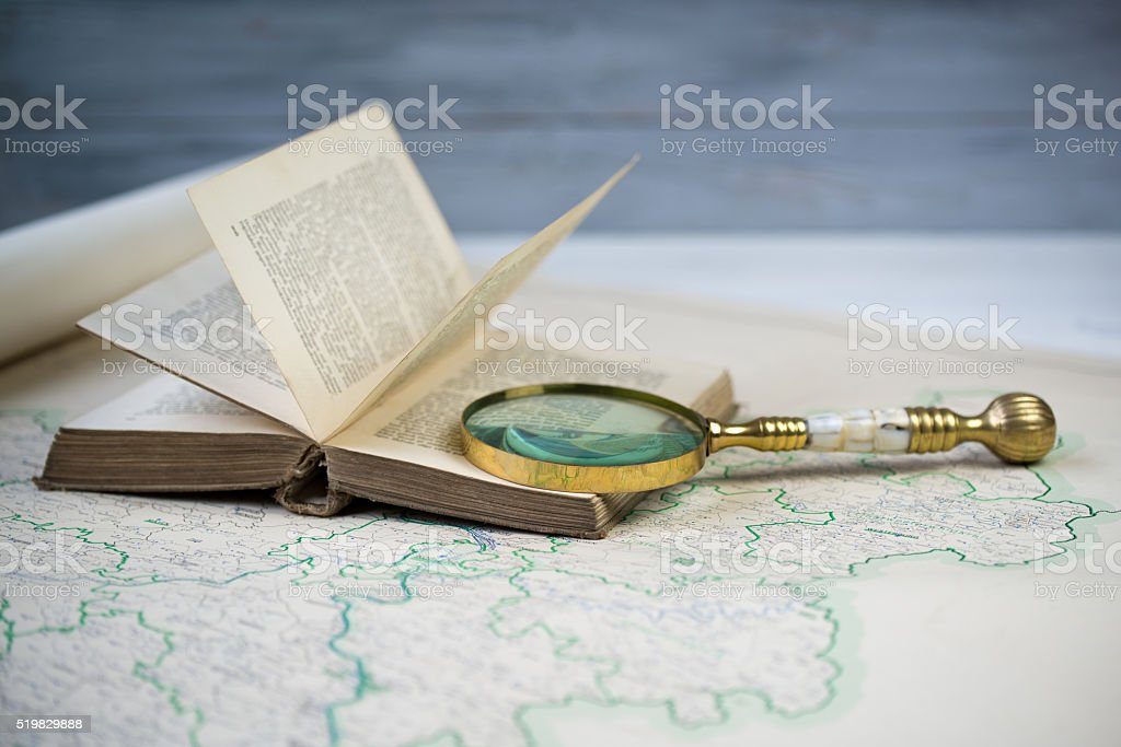 Old beautiful golden magnify glass on ancient book and old map stock photo