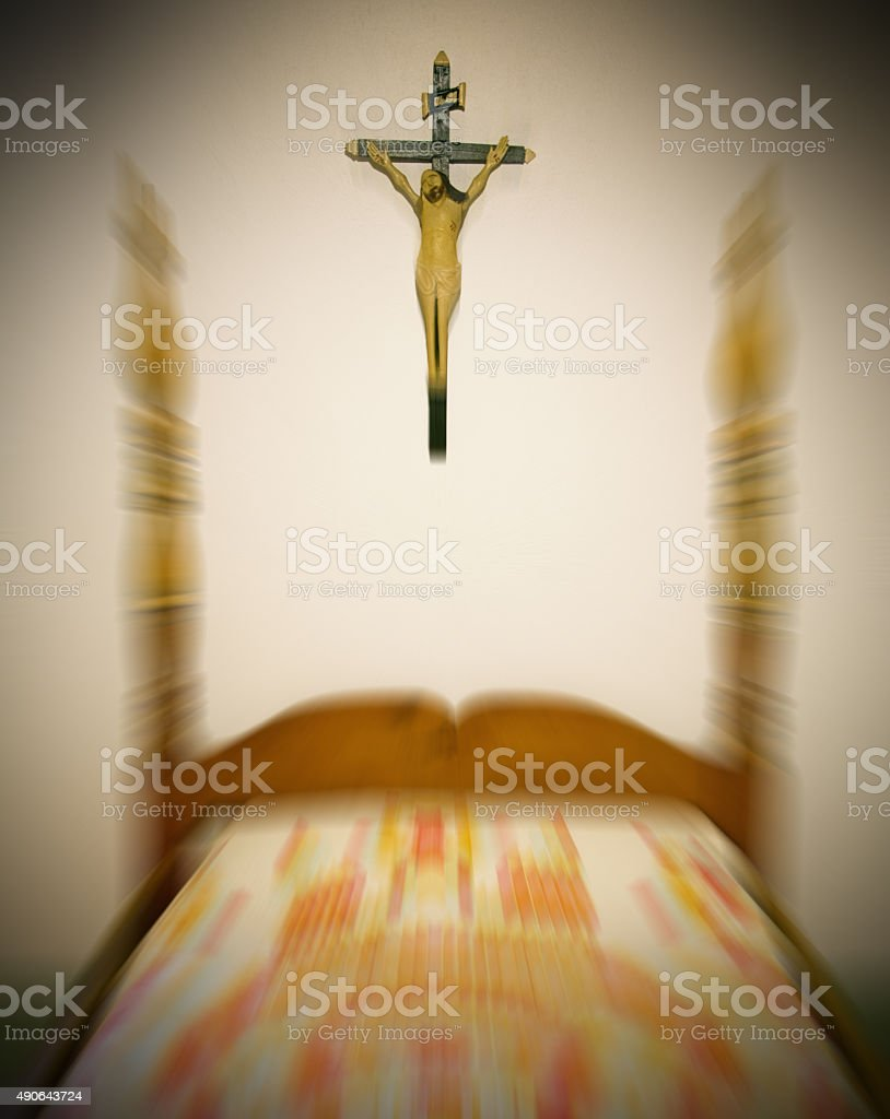 Old  bed with a crucifix above it- zoom effect stock photo