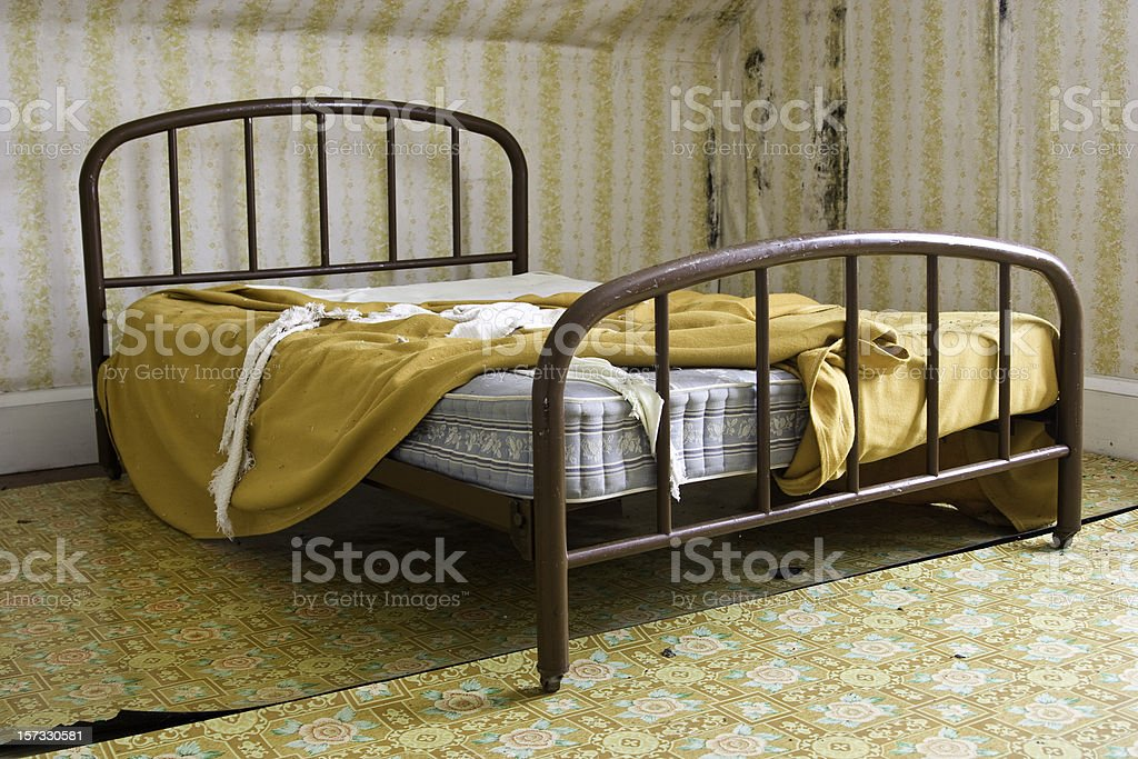 Old Bed with Sheets in Abandoned House stock photo