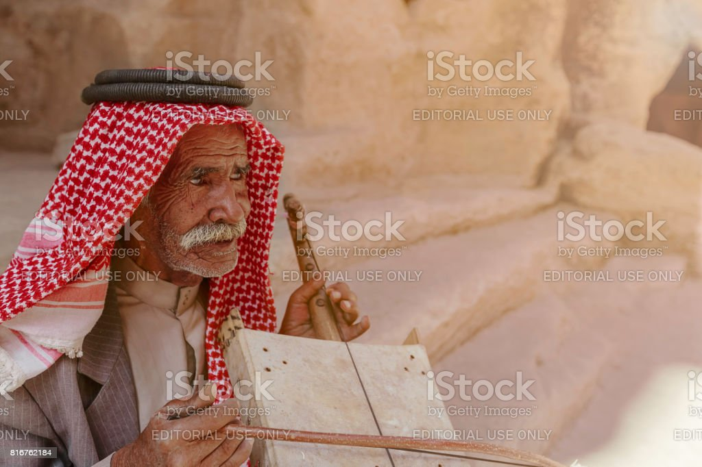 Old Bedouin man or Arab man in traditional outfit, playing his musical instrument at the doorway of Little Petra. stock photo