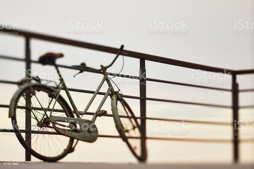 Old bicycle resting on the balaustrade at sunset stock photo