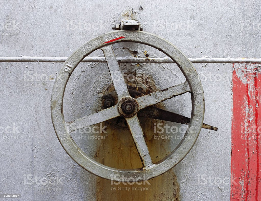 old big hand wheel on the wall of tank stock photo
