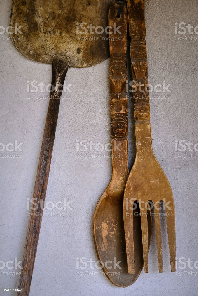 Old big wooden fork and spoon hanging on wall stock photo
