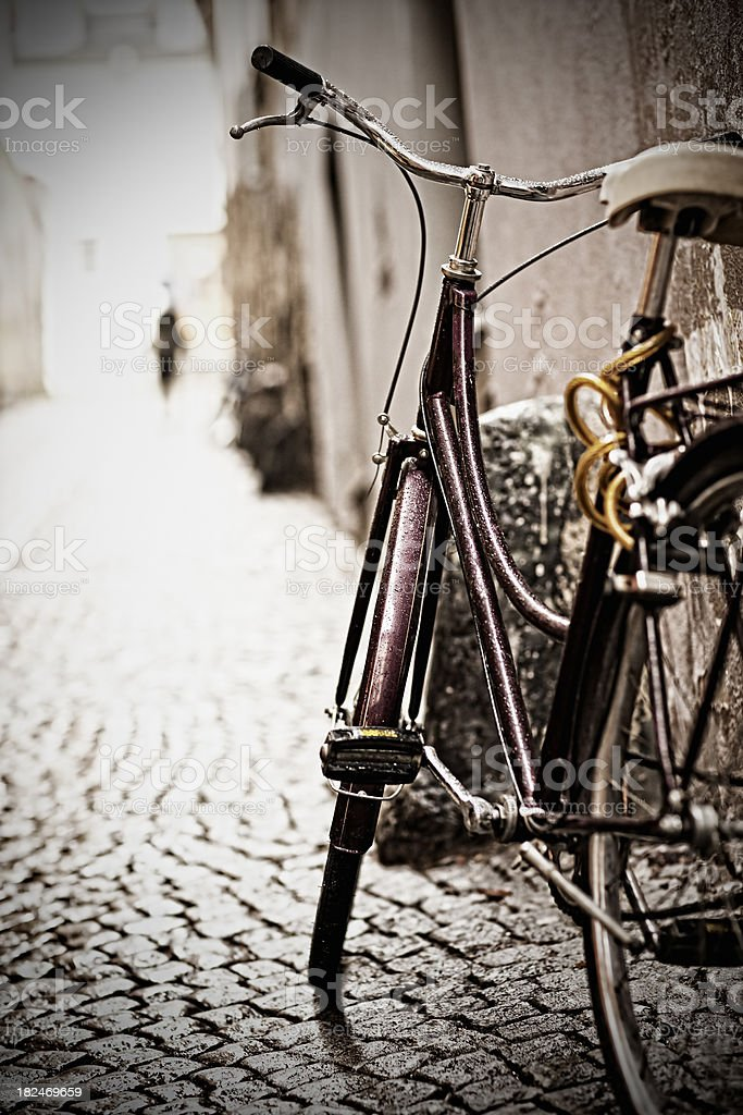Old bike on paved with granite setts royalty-free stock photo