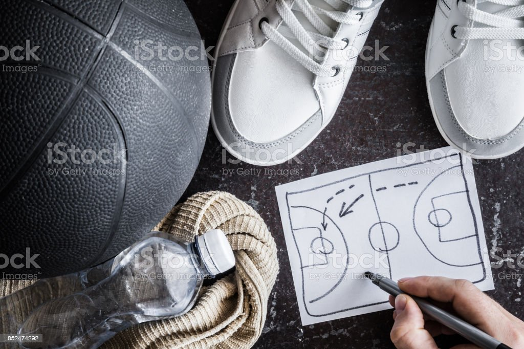 Old, black basketball ball with accessories on the dark floor. Coach creates a game of tactics. Street basketball. Outdoor sport activity. Sport concept. Close up. Vintage retro style and atmosphere. stock photo