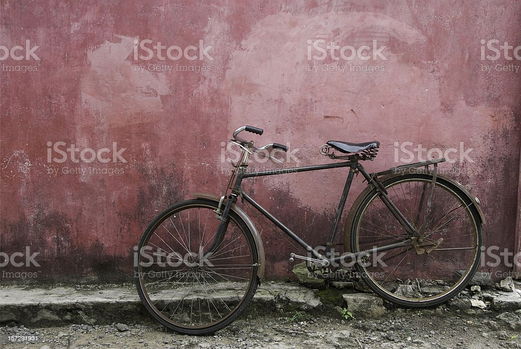 Old black bicycle leaning against grunge pink wall royalty-free stock photo