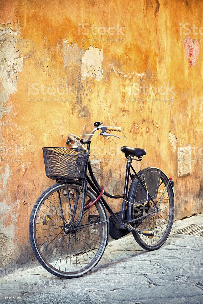 Old black bike against a yellow wall in Tuscany, Italy royalty-free stock photo
