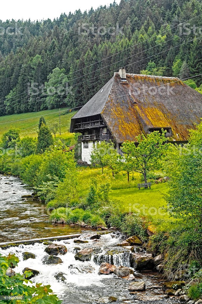 old Black Forest farmhouse on the river stock photo