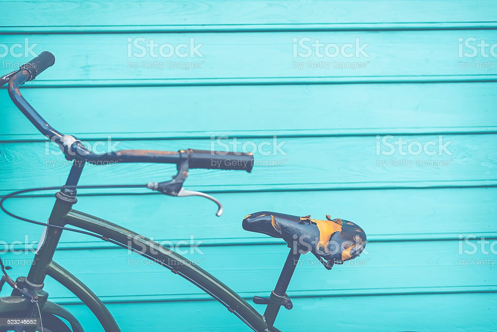 Old black leather of bike seat on blue wood stock photo