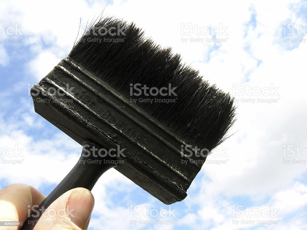 Old black paintbrush in hand against the sky royalty-free stock photo