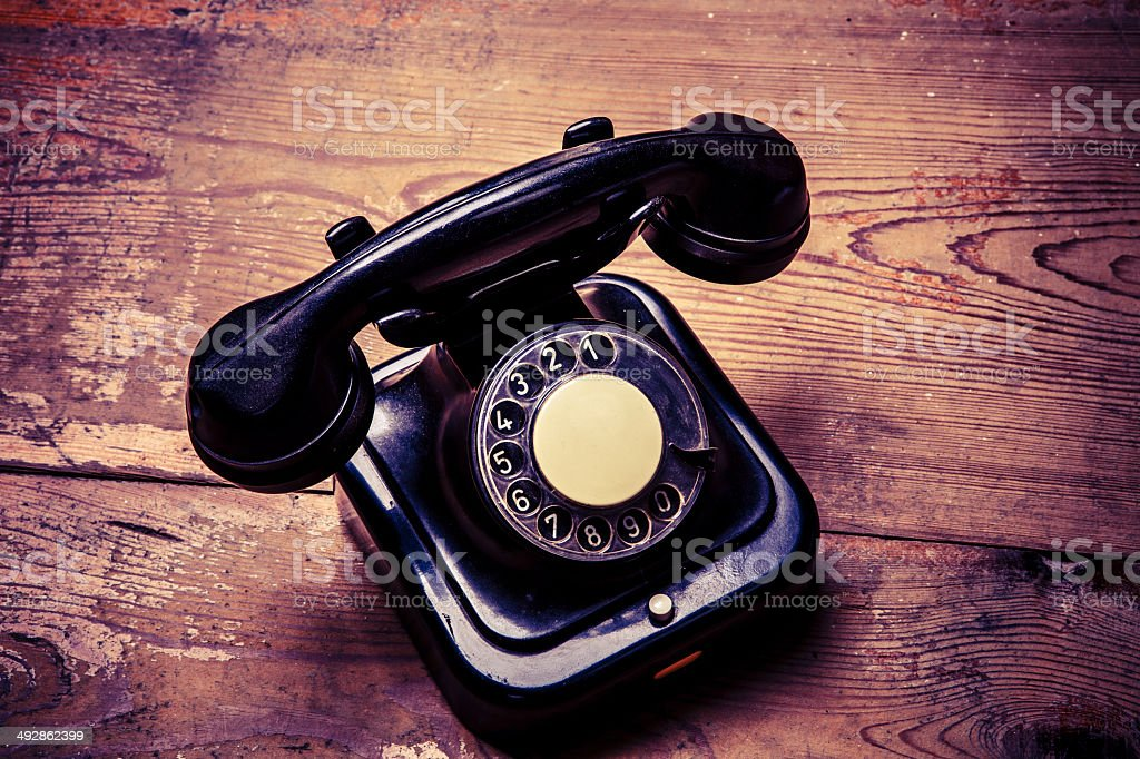 Old black phone with dust and scratches on wooden floor stock photo