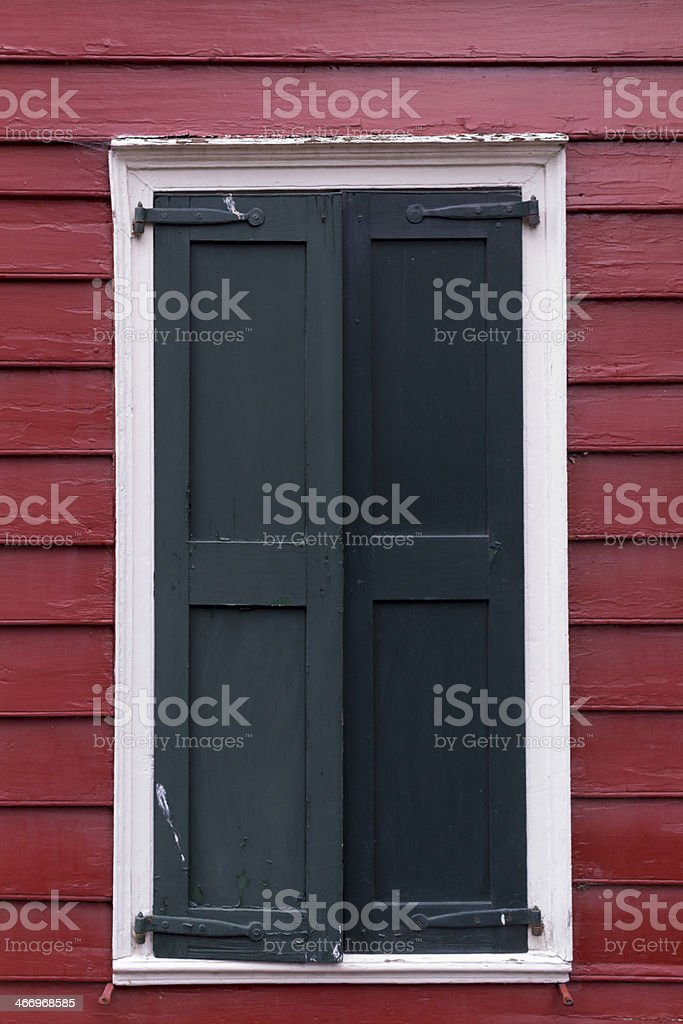 Old Black Shutters Against Red Siding royalty-free stock photo