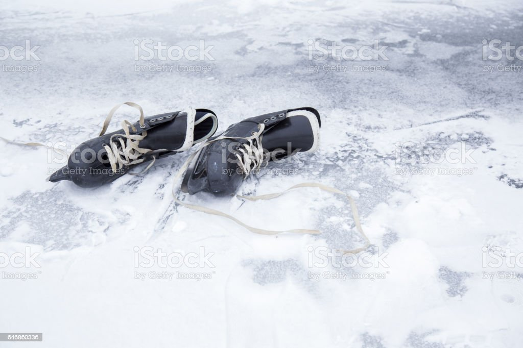 Old black skates on the ice area in winter day. stock photo