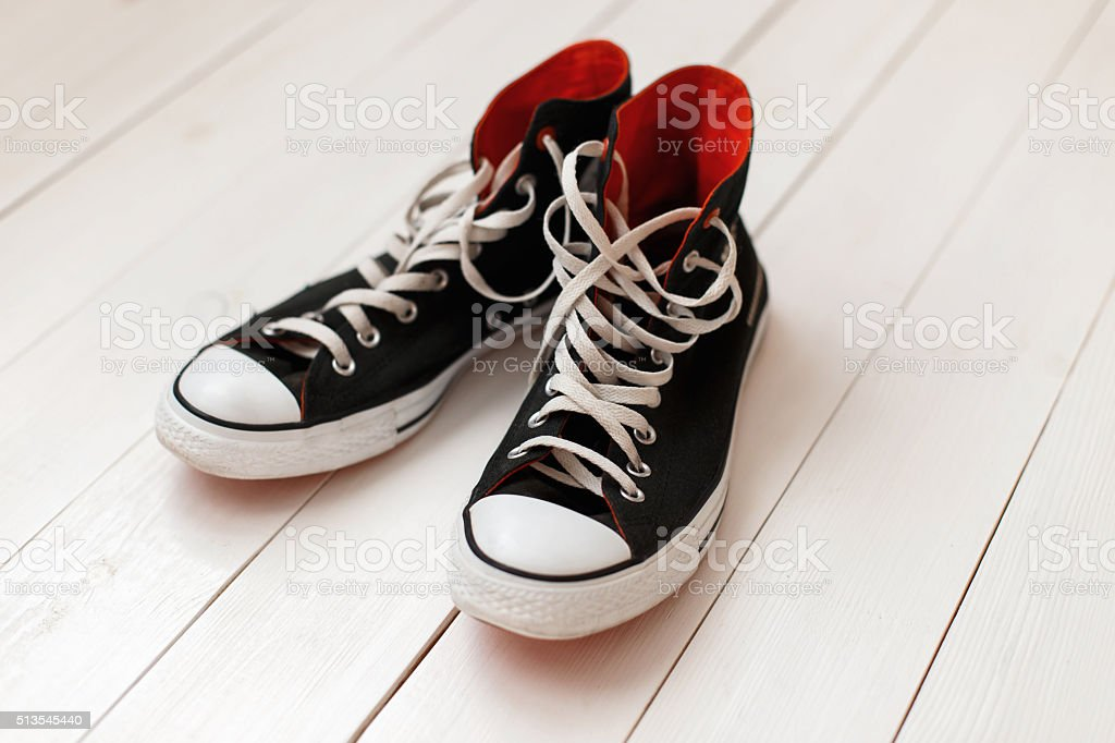 Old black sneakers with red on wooden background stock photo