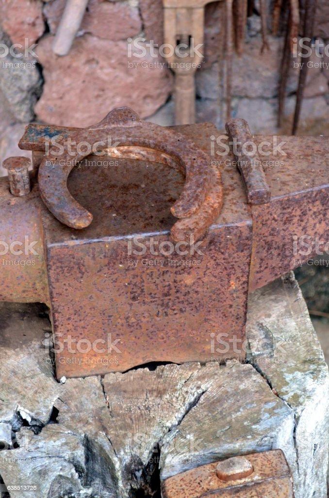 Old blacksmith's anvil with horseshoe stock photo