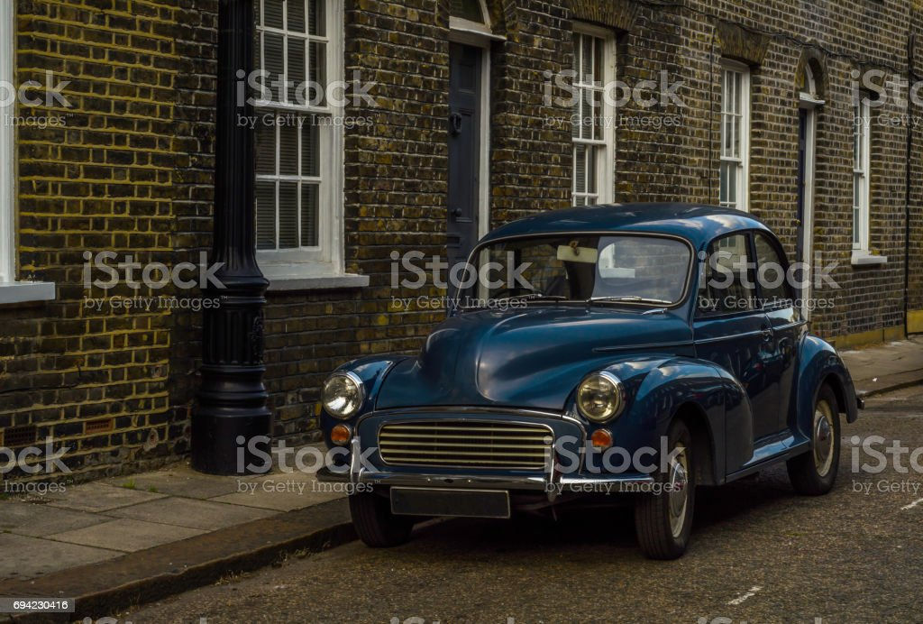 Old blue car parked on the street, old london, old building in london stock photo