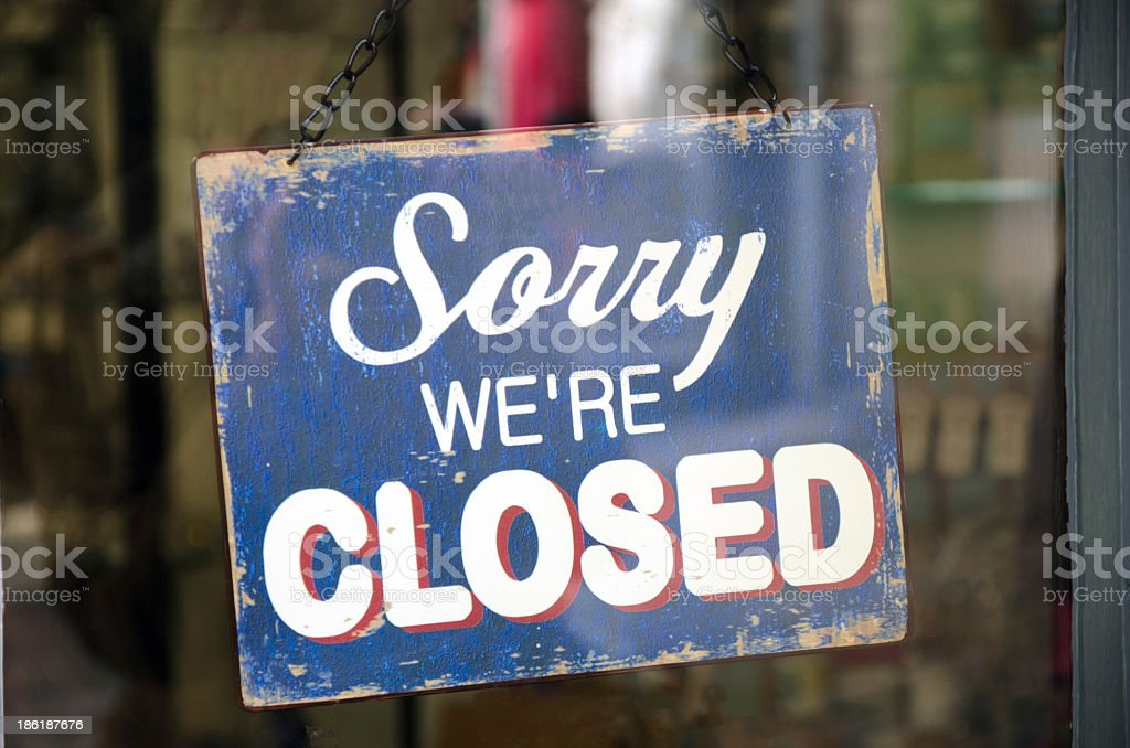 Old blue closed sign hanging in a shop window stock photo