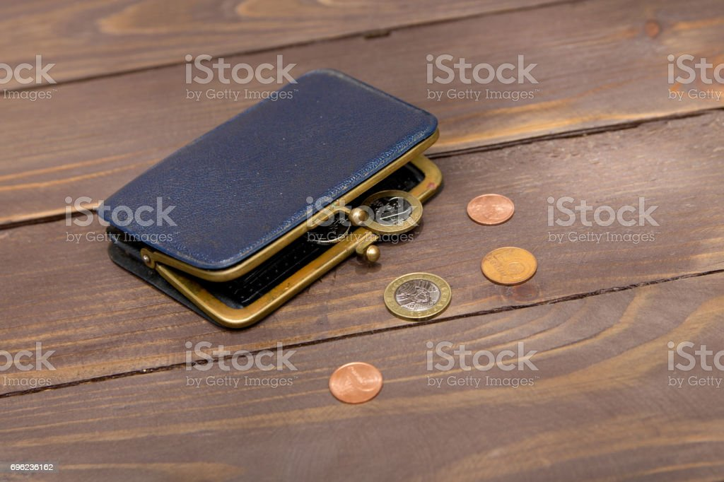 Old blue purse. Open wallet with coins on wooden background. stock photo