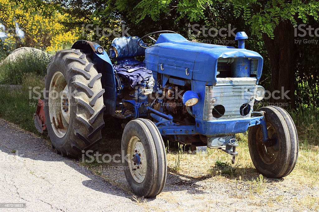 old blue tractor on the road royalty-free stock photo