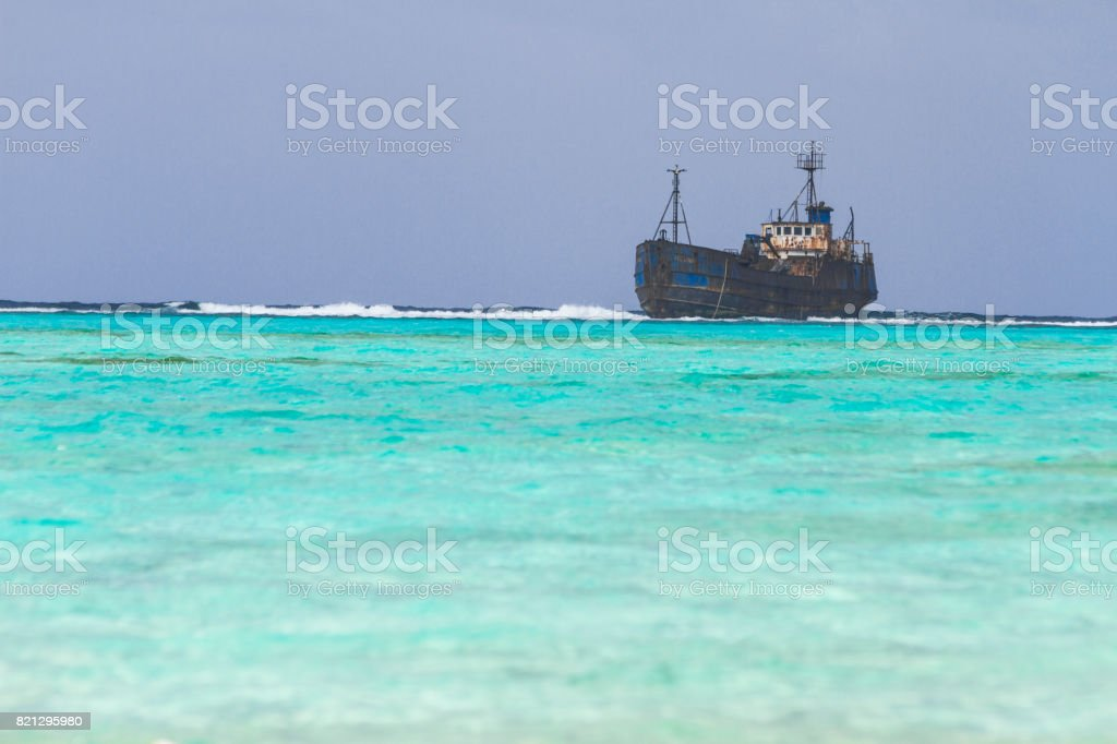 Old boat agrounded over coral reef stock photo