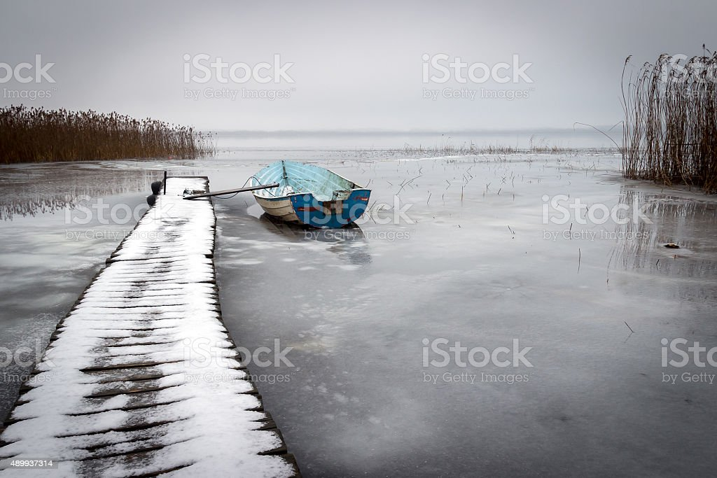 Old boat in a frozen lake winter stock photo