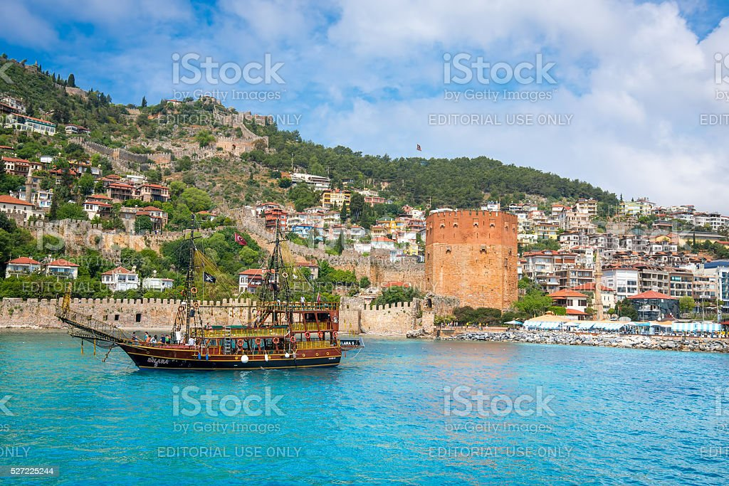 Old boat in front of Red Tower, Alanya, Turkey stock photo