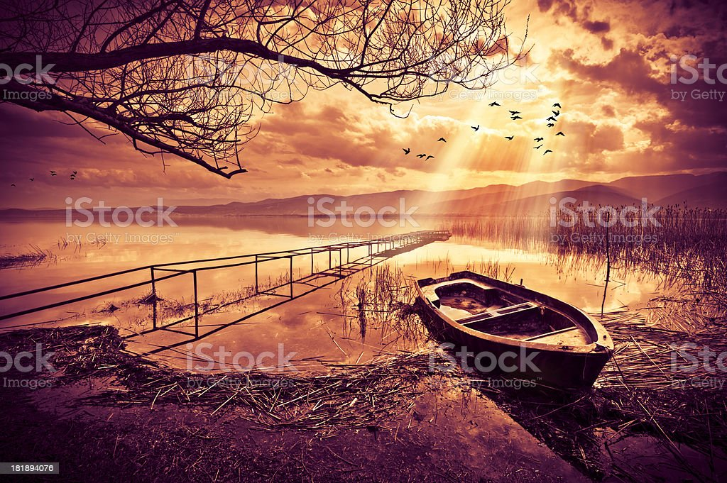 Old Boat on Lake at Sunset stock photo