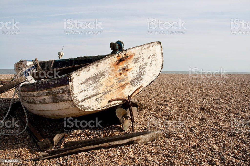Old boat on shingle beach stock photo