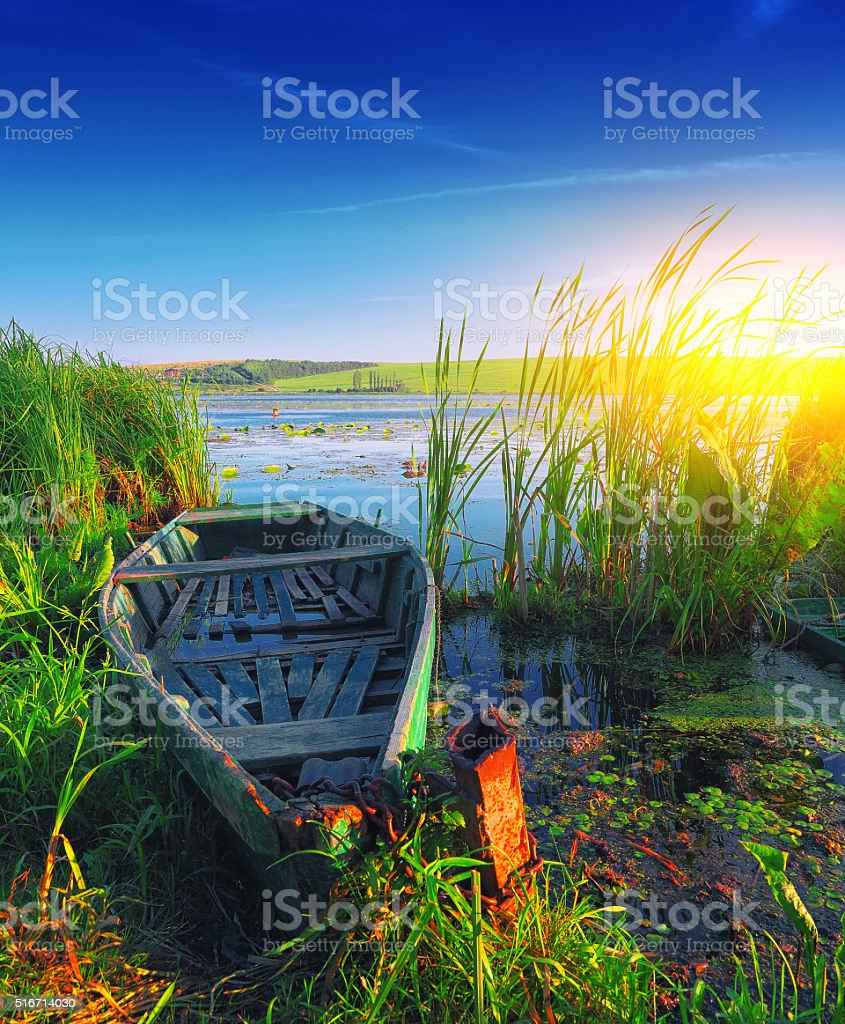 old boat on the lake at sunset stock photo