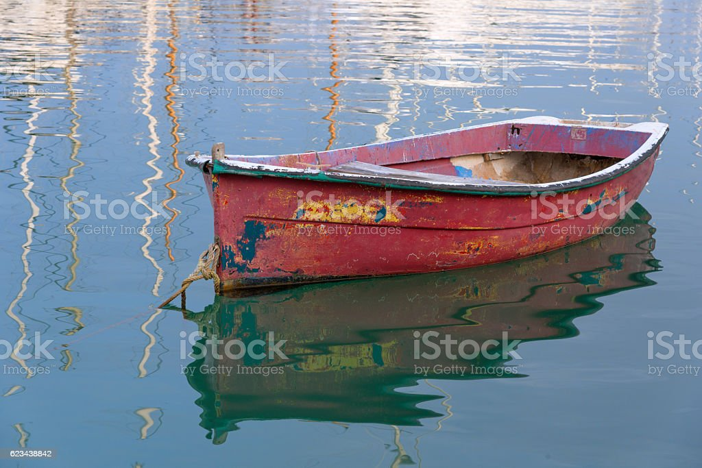 old boat with different old color in harbor stock photo