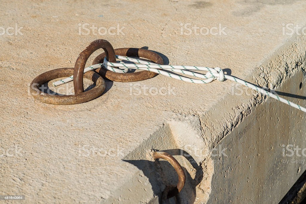 Old bollard with the rope stock photo