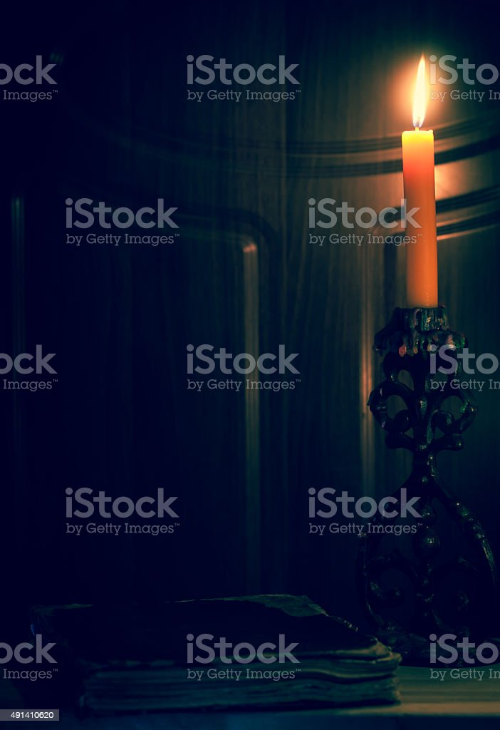 Old book and  burning candle. Vintage photo. stock photo