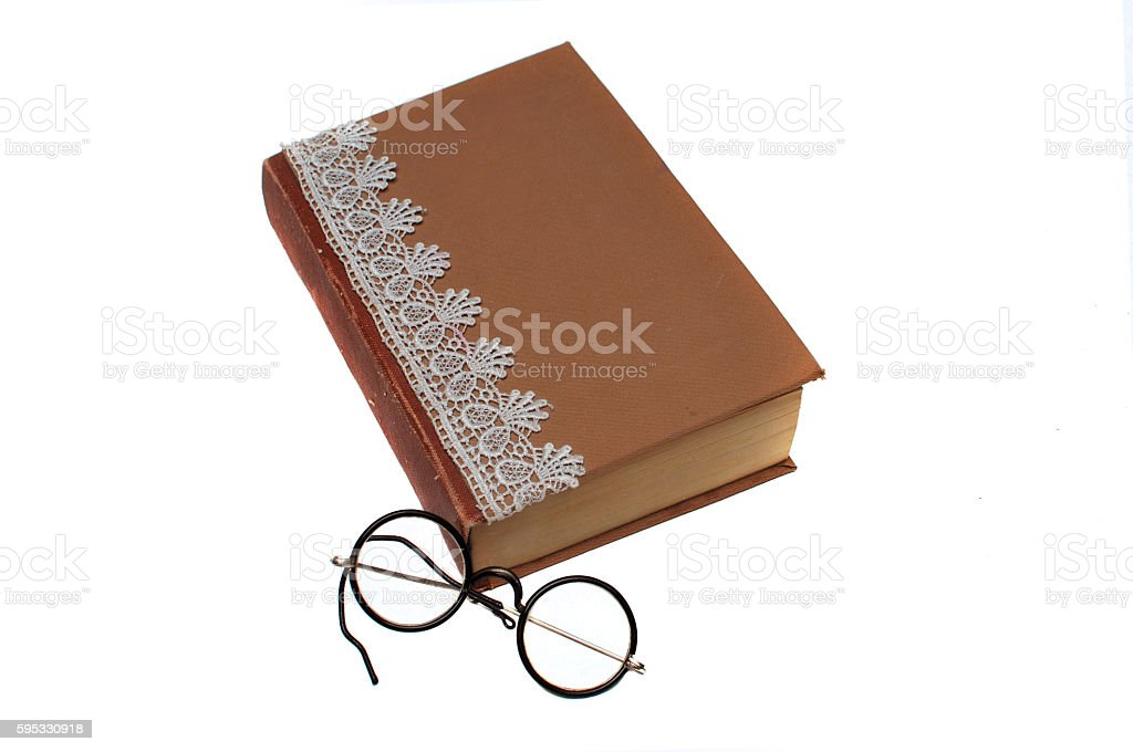 Old book and vintage round reading glasses stock photo