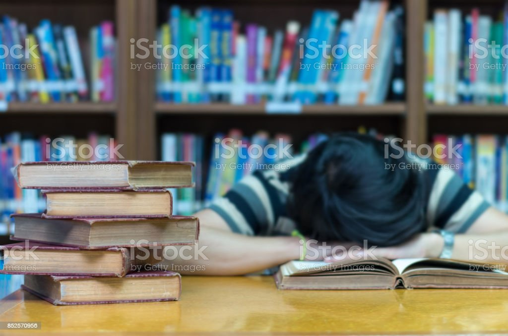 old book on the desk in library with the man sleeping over the book background stock photo
