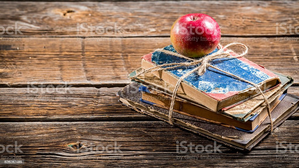 Old books and apple on school desk stock photo