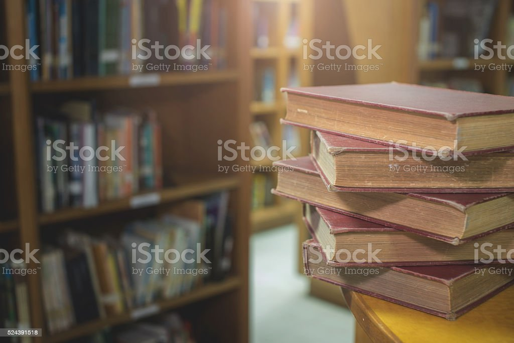 old books on a wooden desk in library room stock photo
