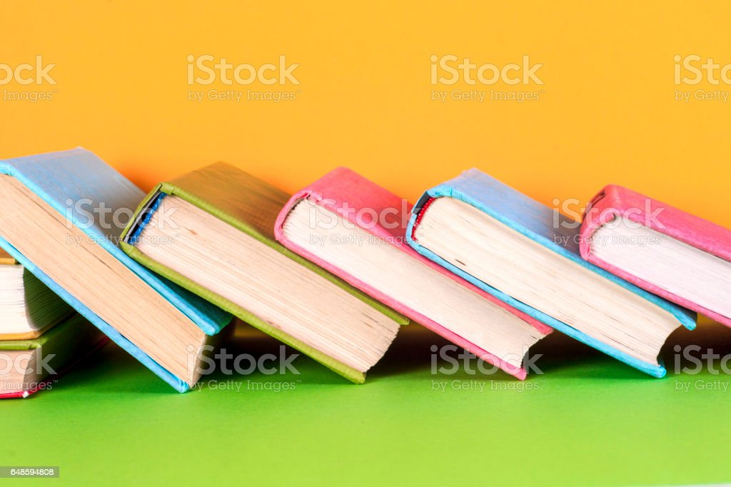 Old books on a wooden shelf. No labels, blank spine. stock photo
